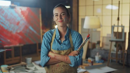 Aufkleber - Professional Young Female Artist Dirty with Paint, Wearing Apron, Arms Crossed while Holding Brushes, Looks at the Camera with a Smile. Authentic Creative Studio with Large Canvas. Face Portrait
