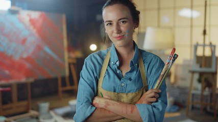Fototapete - Talented Female Artist Dirty with Paint, Wearing Apron, Crosses Arms while Holding Brushes, Looks at the Camera with a Smile. Authentic Creative Studio with Large Canvas. Head and Shoulders Portrait