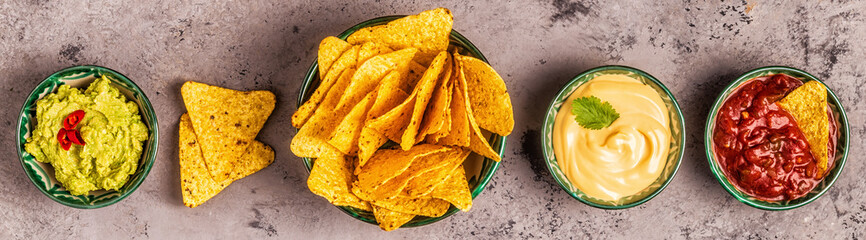 Mexican food background: guacamole, salsa, cheesy sauces with nachos