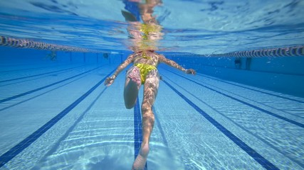 Fototapete - Woman swimming in the poolin the olympic Swimming pool view from under water
