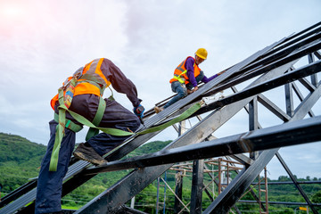 Roofer worker in protective uniform wear and gloves, using air or pneumatic nail gun and installing asphalt shingle on top of the new roof,Concept of residential building under construction. Wall mural