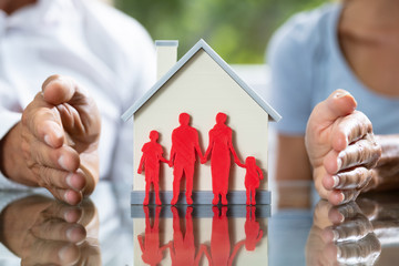 Couple Protecting Family Cutout And House Model