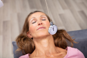 Woman Being Hypnotized While Lying On Sofa
