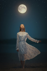 Young attractive girl holds a tied moon on a rope. Art photo.