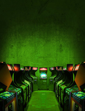 Old Unbranded Vintage Arcade Video Games in a dark gaming room with green light with glowing displays and concrete wall - vertical photo of retro design with free copy space for a poster or magazine