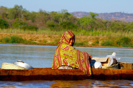 Malagasy woman crossing the inlets in an outrigger canoe