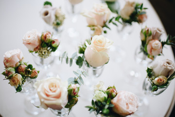 Top-down picture of cream roses in wine glasses