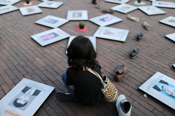 A boy looks at pictures of missing people displayed on the ground during a demonstration marking the International Day of the Victims of Enforced Disappearances, in Bogota
