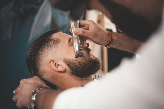 Barber makes a beard cut for a client. Hipster client visited barbershop