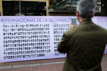 A man takes a picture with his cell phone to a banner with pictures of missing people during a demonstration to mark International Day of the Victims of Enforced Disappearances, in Bogota