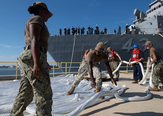 Sailors assigned to Naval Station Mayport lay down mooring lines as the amphibious dock landing ship USS Ft. McHenry  is moved in preparation for Hurricane Dorian at Naval Station Mayport, in Jacksonville