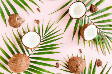 Wall Mural - Pattern, texture with coconuts and tropical palm leaves on pink background. Tropical abstract background. Flat lay, top view.