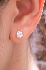 Gold earrings stud with diamonds macro shot.
