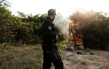 A federal police officer looks on as machines are destroyed during an operation conducted jointly with the Brazilian Institute for the Environment and Renewable Natural Resources (IBAMA) at an illegal gold mine near the city of Altamira