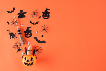 Top view of Halloween crafts, orange pumpkin, ghost, bat and spider on orange background with copy space for text. halloween concept. Fototapete