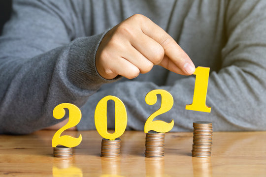 2021 New year saving money and financial planning concept. Female hands putting gold wooden number 2021 on stack of coins. tax payment, investment and banking.