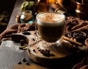 foamy pumpkin spice latte in glass jar on wooden board on rustic brown table