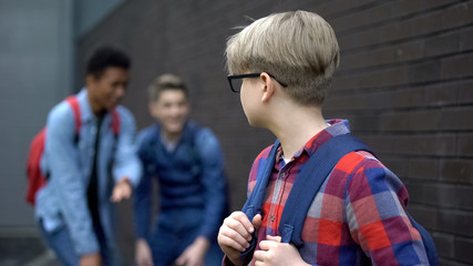 Cruel teenagers laughing at new boy in school, calling names, verbal bullying