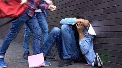 Cruel teenagers scattering classbooks of afro-american boy, school bullying