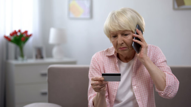 Sad old woman with credit card calling bank support, reporting about money fraud