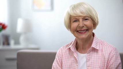 Happy elderly woman smiling at camera, social security, retirement benefits