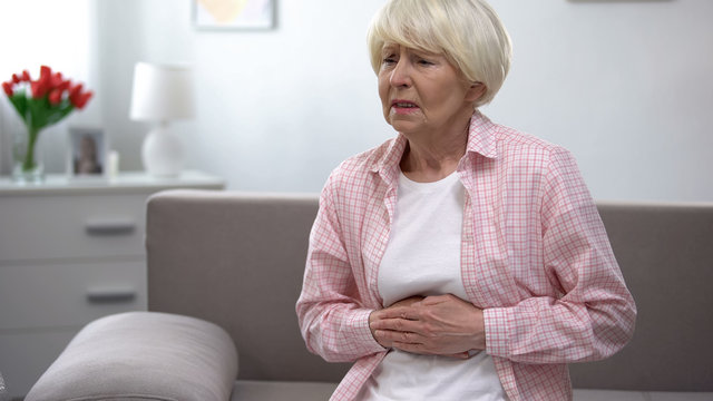 Senior woman suffering from epigastria pain, health problems in old age
