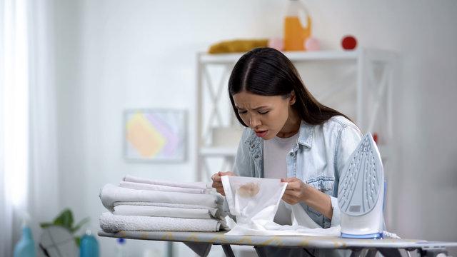 Upset female makes burn stain on shirt during ironing, housekeeping problem