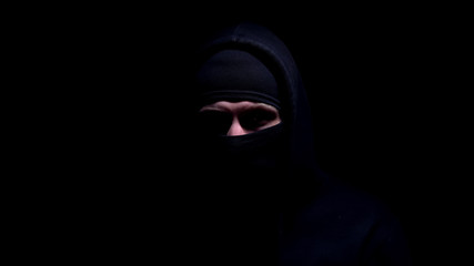 Spooky man in balaclava and hood looking into camera, member of gangster group - fototapety na wymiar