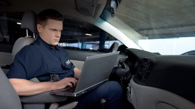 Policeman working on laptop in patrol car, monitoring incident map, technology