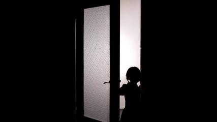 Little female child silhouette opening door into darkness, horror scene, mystic