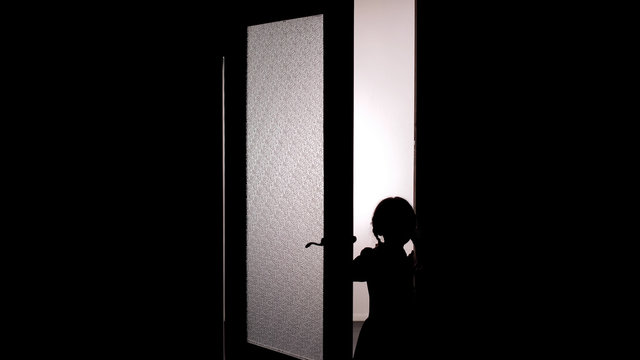 Little female child silhouette opening door into darkness, horror scene, mystic
