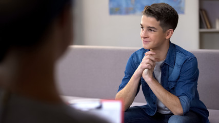 Tricky teen boy with gloating smile visiting psychologist, behavior modification