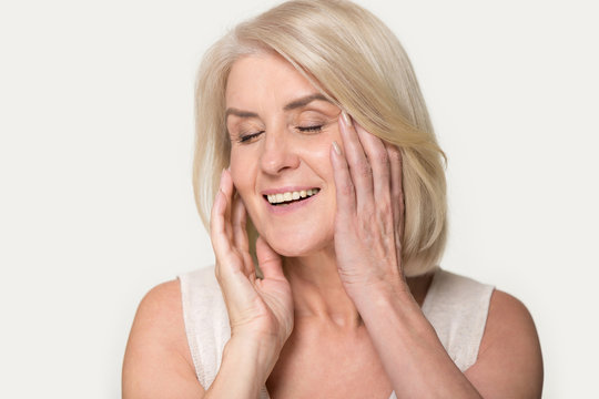 Smiling senior woman touch healthy face skin after beauty procedure