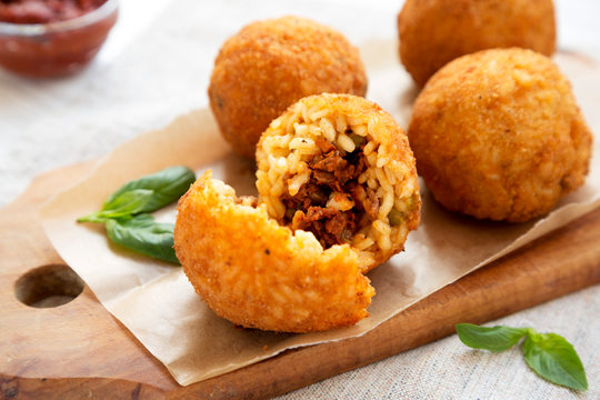 Homemade fried Arancini with basil and Marinara on a white wooden background, side view. Italian rice balls. Closeup.
