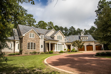 Front view of large estate home in the south with a gravel driveway and lots of windows. house made of brick, stone and clapboard in a cape cod style. and a triple garage with curb appeal Wall mural