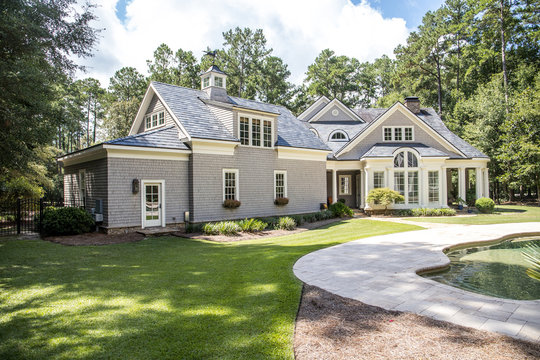Rear view and backyard of large cape cod style home with columns and windows and a round porch patio