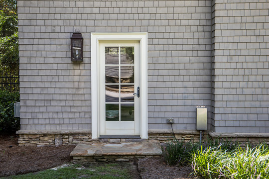 cape cod style home with white wood door at back entrance. Door has many glass windows and outside is an exterior light