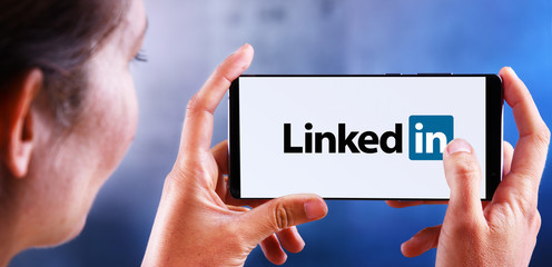 Woman holding smartphone displaying logo of LinkedIn