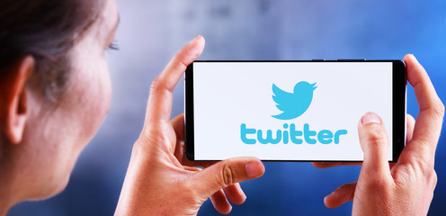Woman holding smartphone displaying logo of Twitter