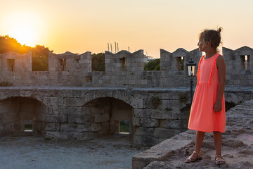 A little girl on fortress wall looks at the setting sun. Mandraki, Old Town, Rhodes. Sunset
