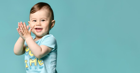 Full length portrait of a toddler boy in a blue summer cotton suit isolated in a turquoise background.