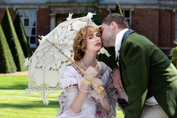 Young couple dressed in vintage costume relaxing and kissing on lawn of stately home Wall mural