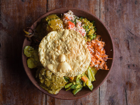 Bowl of variety of traditional vegan Sri Lankan food with different curries, papadum, rice, sambol, dal and vegetables, Ella, Sri Lanka.