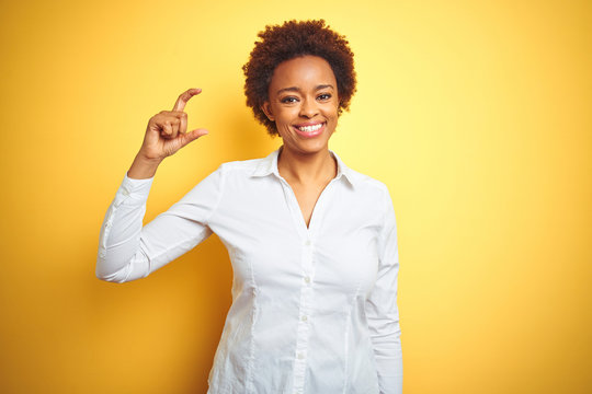 African american business woman over isolated yellow background smiling and confident gesturing with hand doing small size sign with fingers looking and the camera. Measure concept.