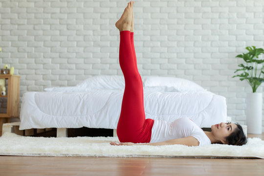 Happy Attractive Asian woman practice yoga leg raises pose with meditation smile with big belly after wake up in the morning Feeling so comfortable and relax,Healthcare Concept