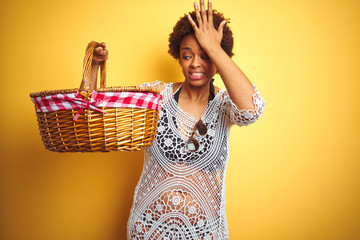 Young african american woman holding picnic basket on vacation over isolated yellow background stressed with hand on head, shocked with shame and surprise face, angry and frustrated. Fear and upset