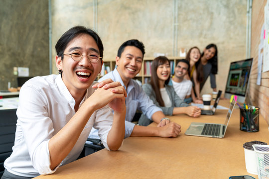 Happy asian man and creative team are smiling and looking at camera in modern workspace office. Happy group of confident employee in cowork. Relation and engagement concept.