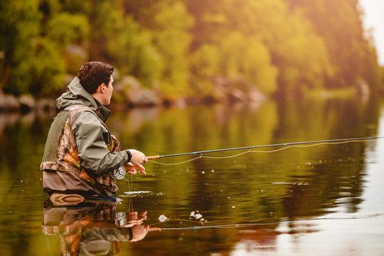 Fisherman using rod fly fishing in mountain river summer splashing water