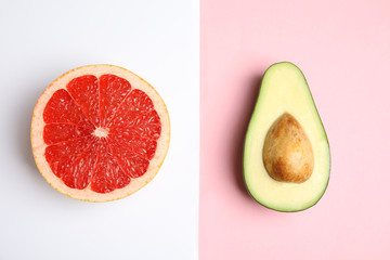 Cut ripe avocado and grapefruit on color background, flat lay