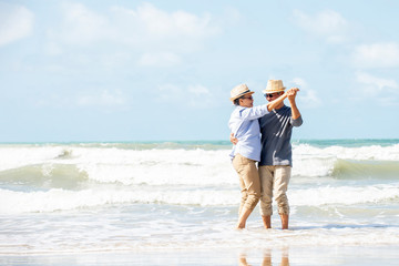 Happy asian senior couple  have fun and enjoy at the beach, senior man and woman dancing on the beach , Retirement Lifestyle Healthy  Travel Vacation Concept